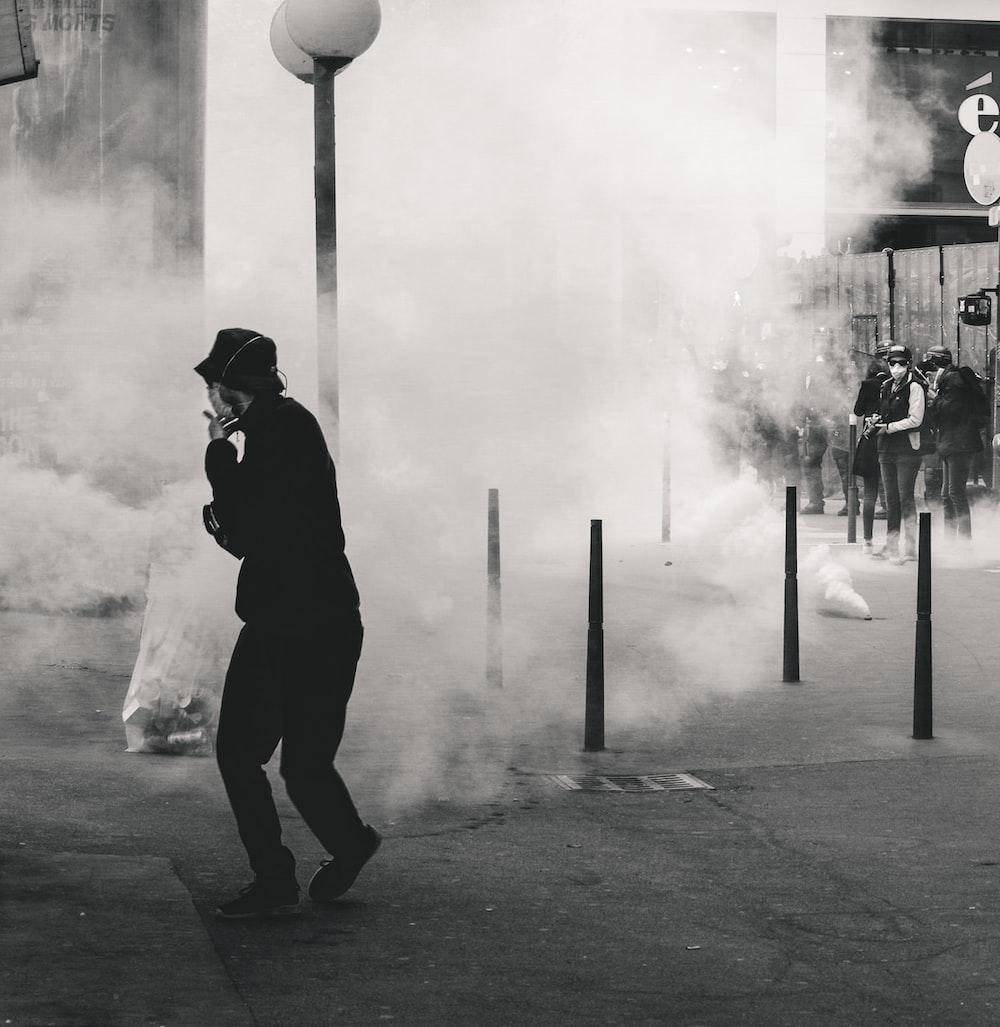 grayscale photo of man near smoke