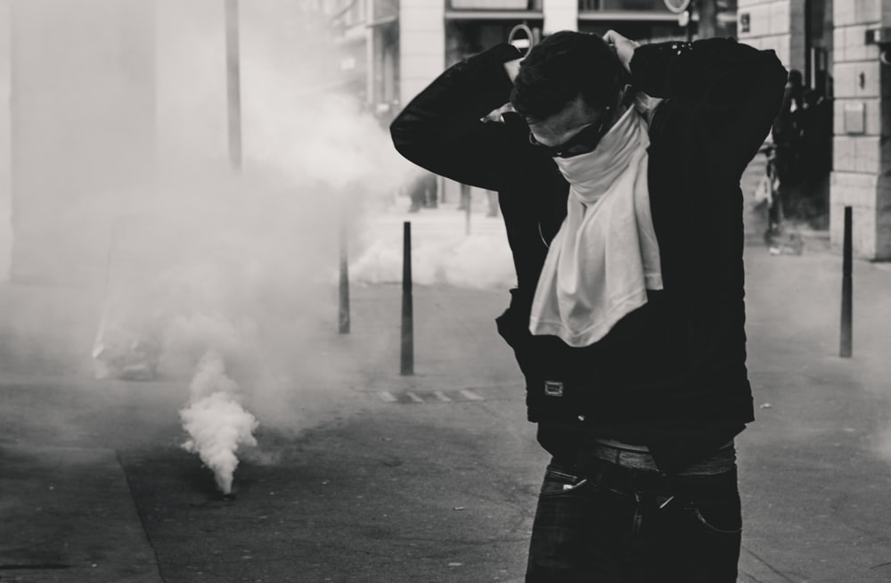 man standing and covering his face using shirt