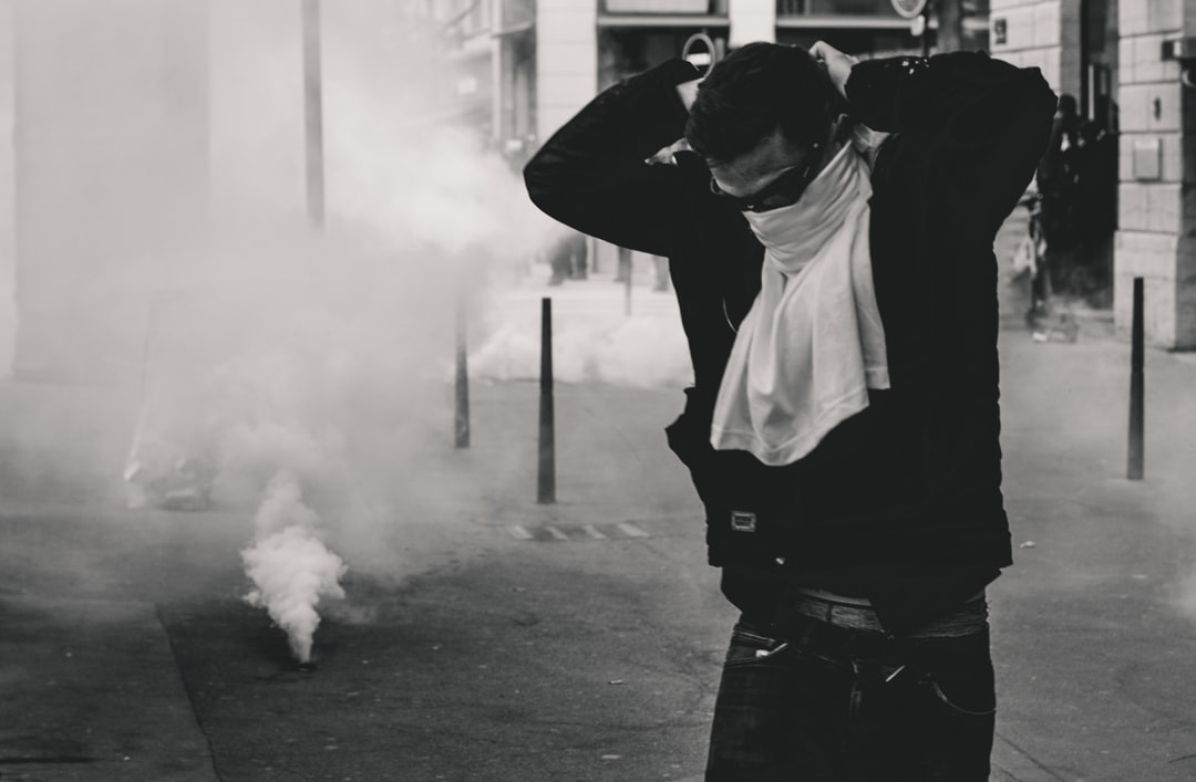 "Police fires tear gas grenades on protestors on the streets of Lyon, France, during the 25th weekend of Yellow Vest protests. A protestor tries to protect himself and prevent the harmful gas to reach his airways. Protestors are no longer allowed to wear face or head protection according to a law, enacted by the French government as a reaction to the riots. CS (or tear gas) is not just itching powder, but nerve gases, that react to moisture and activate pain. It ""can cause severe pulmonary damage and can also significantly damage the heart and liver"" (source: Wikipedia, http://tiny.cc/86f95y)"