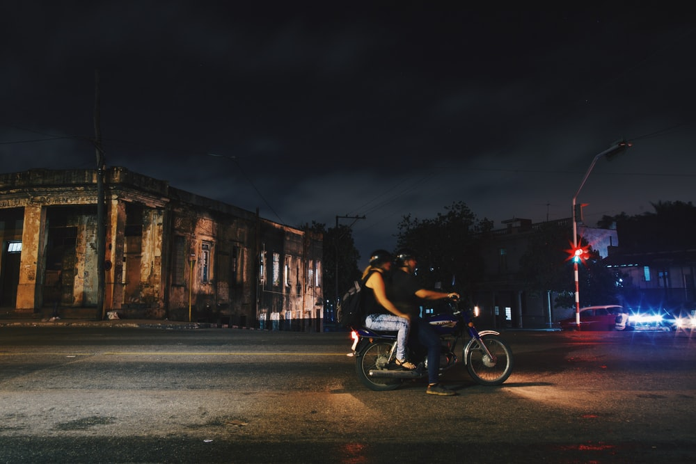 man and woman riding motorcycle at night
