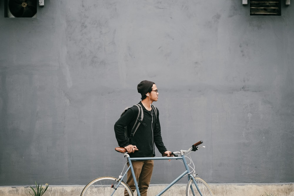 man standing and holding near gray fixie bike