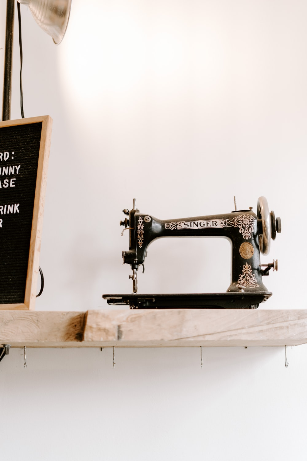 black and brown Singer sewing machine near wall