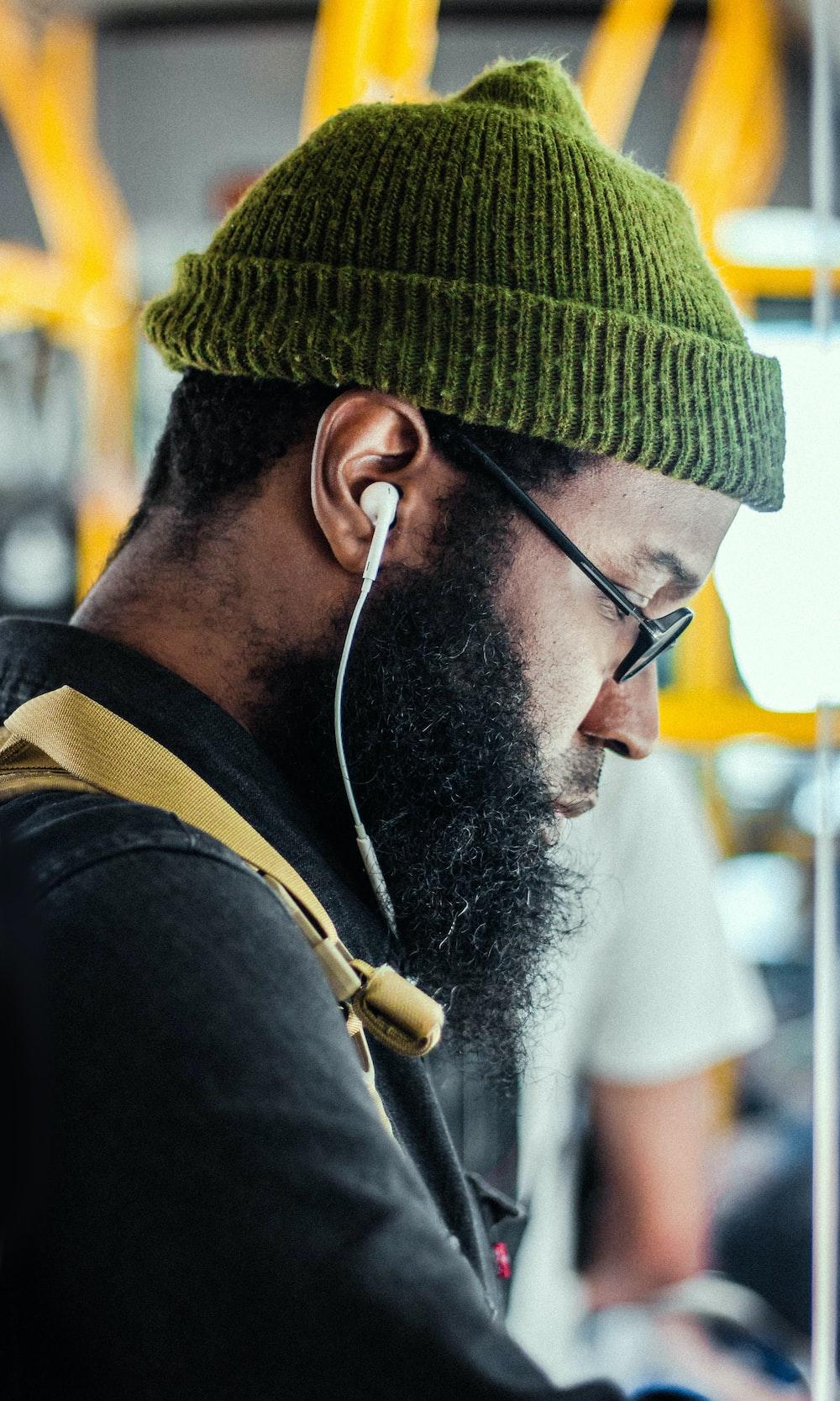 man wearing green knit cap using Apple EarPods