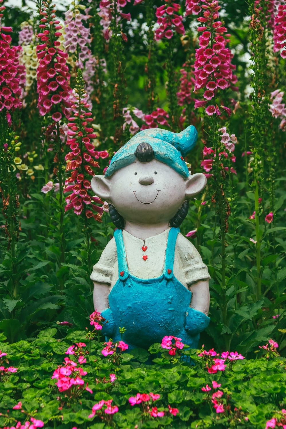 shallow focus photo of boy wearing blue hat statue near pink flowers