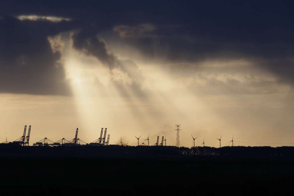 silhouette of windmills under cloudy sky