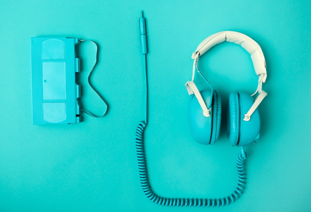 teal and white corded headset near VHS tape