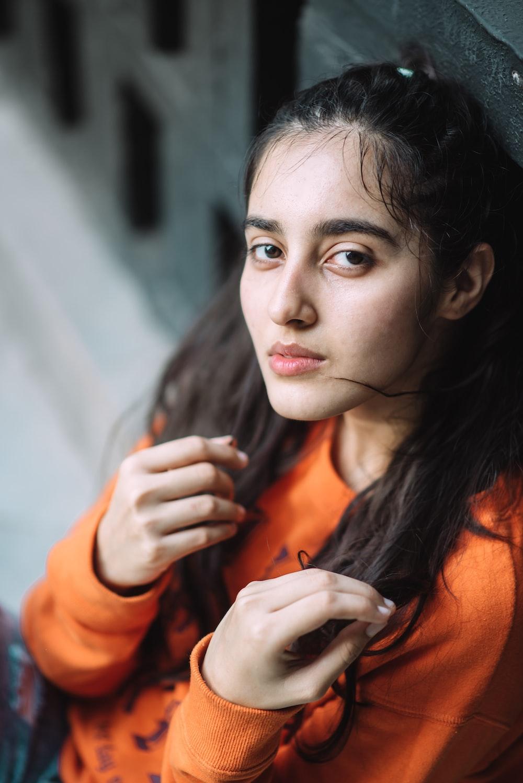 woman wearing orange crew-neck long-sleeved shirt