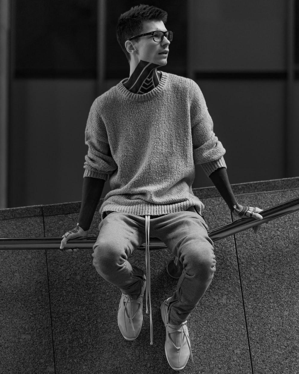 man in sweater sitting on railings