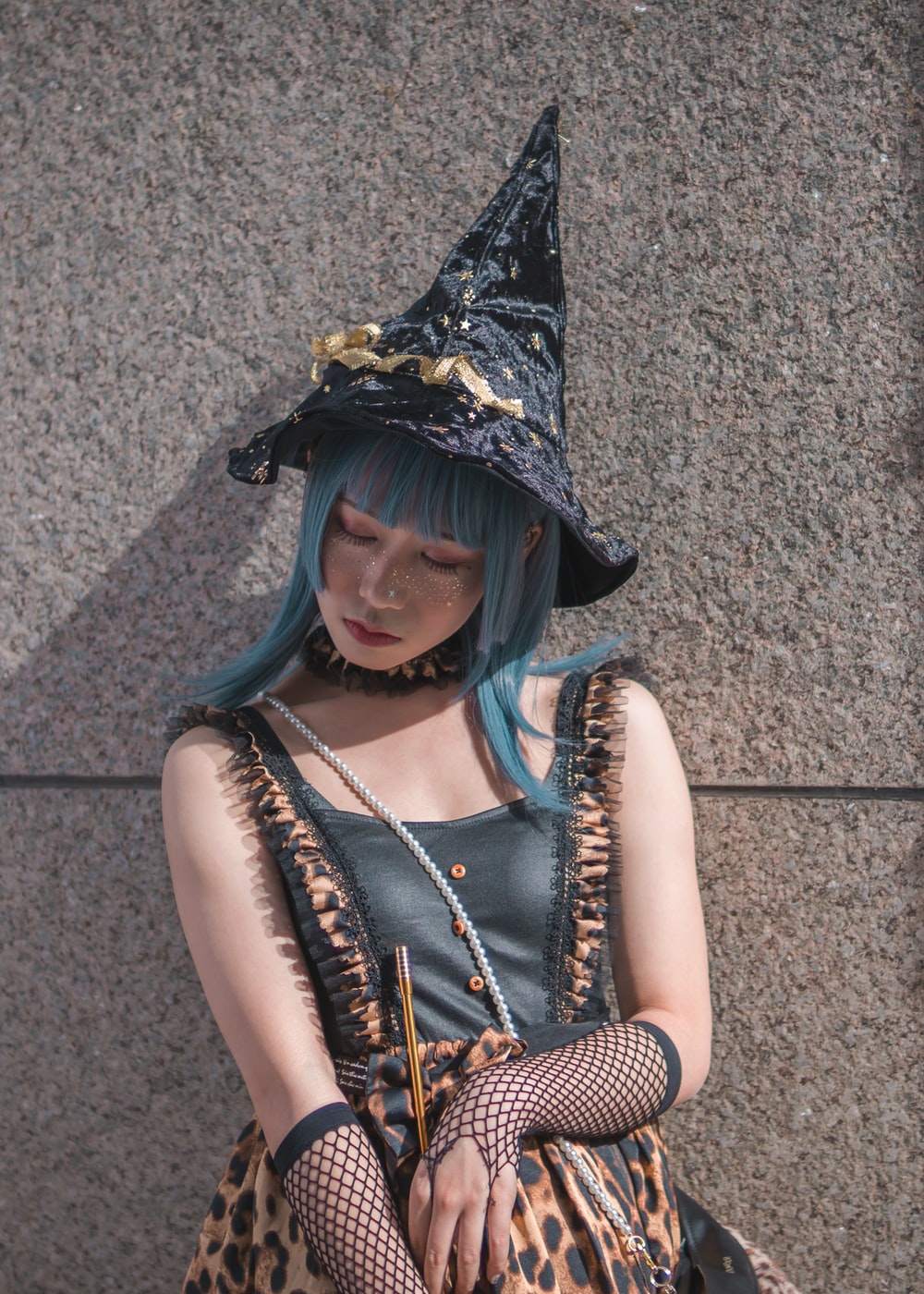 woman wearing witch costume leaning on gray wall