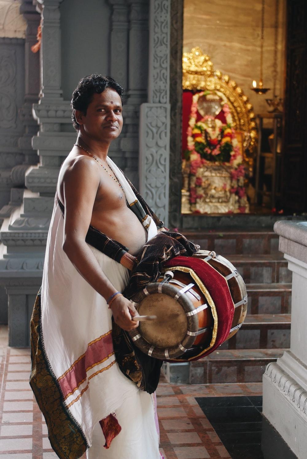 man wearing white dress holding musical drum