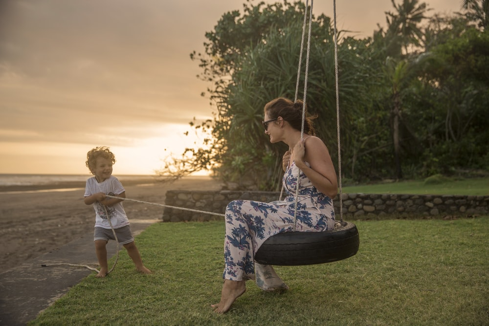 woman on tire swing pulled by boy