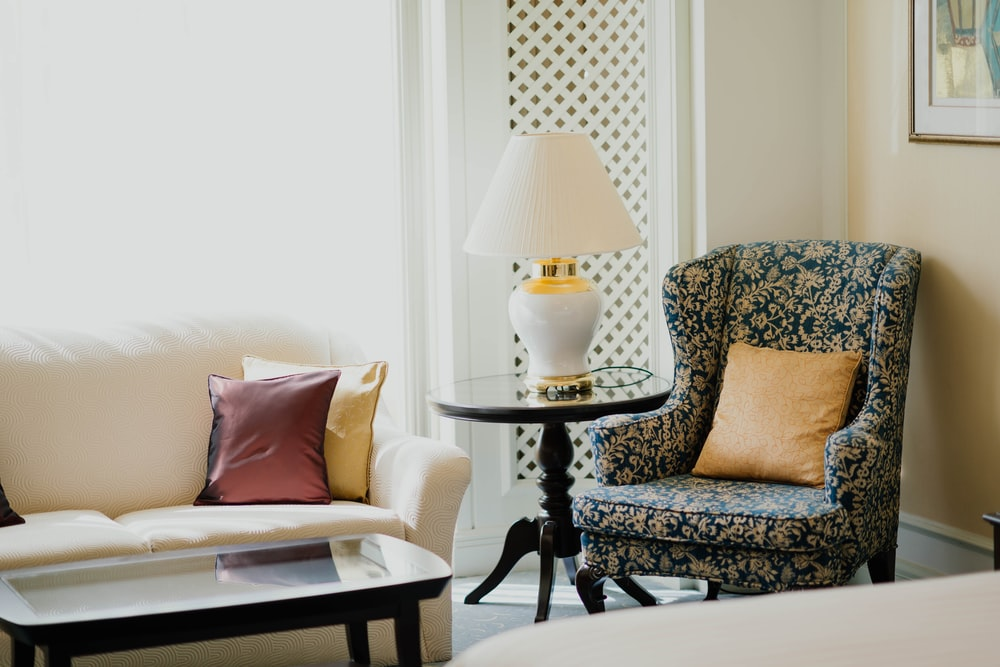 white and gold table lamp on round table in between sofa chair and sofa