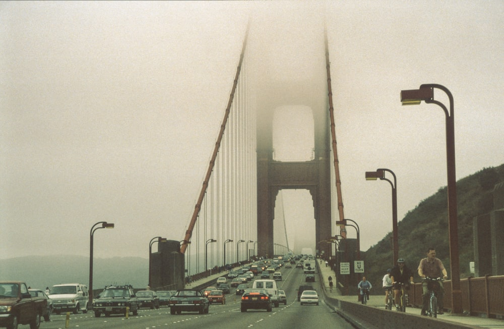 cars travelling on Golden Gate bridge covered in grey fogs