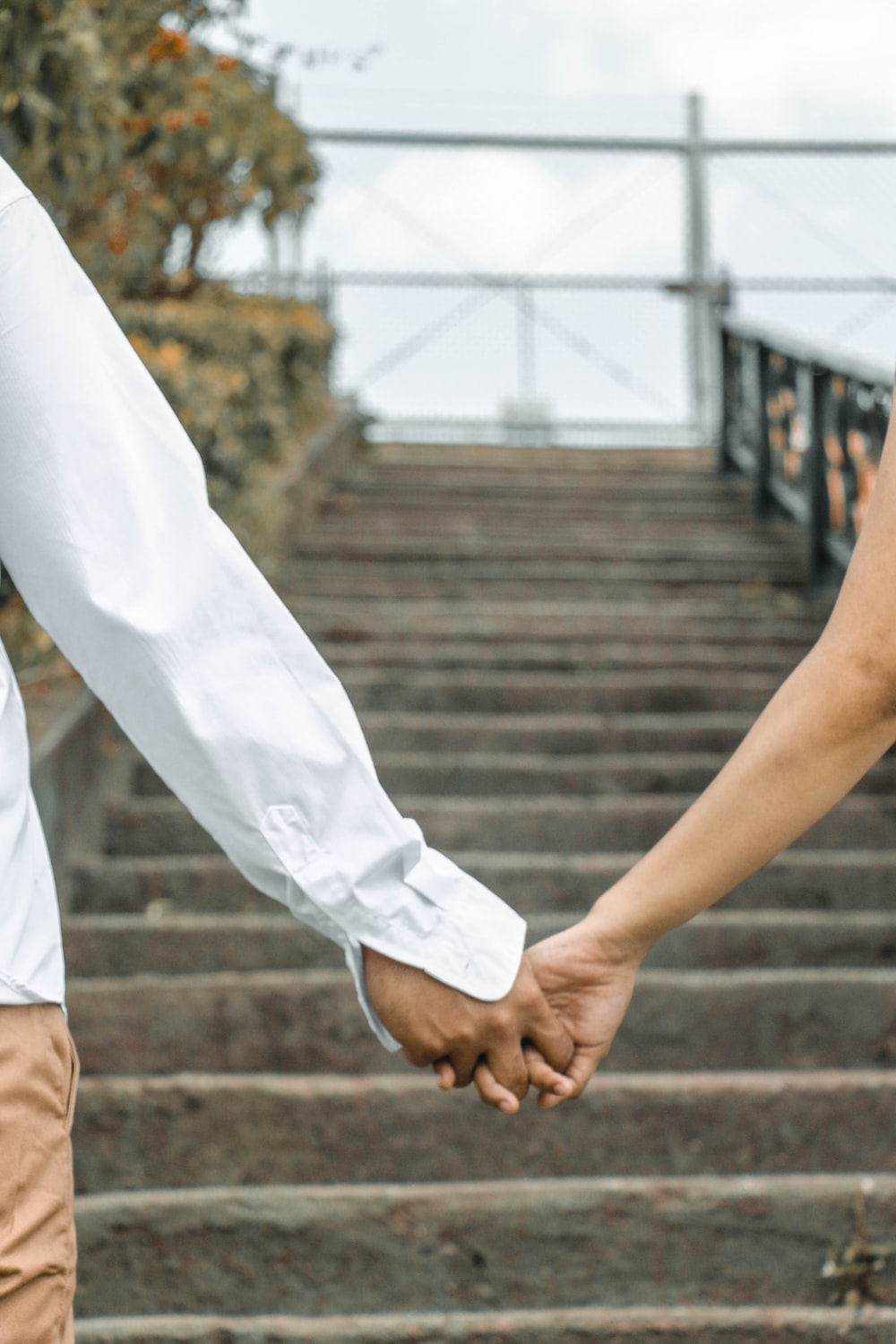 couple holding hand by the stairs outdoors