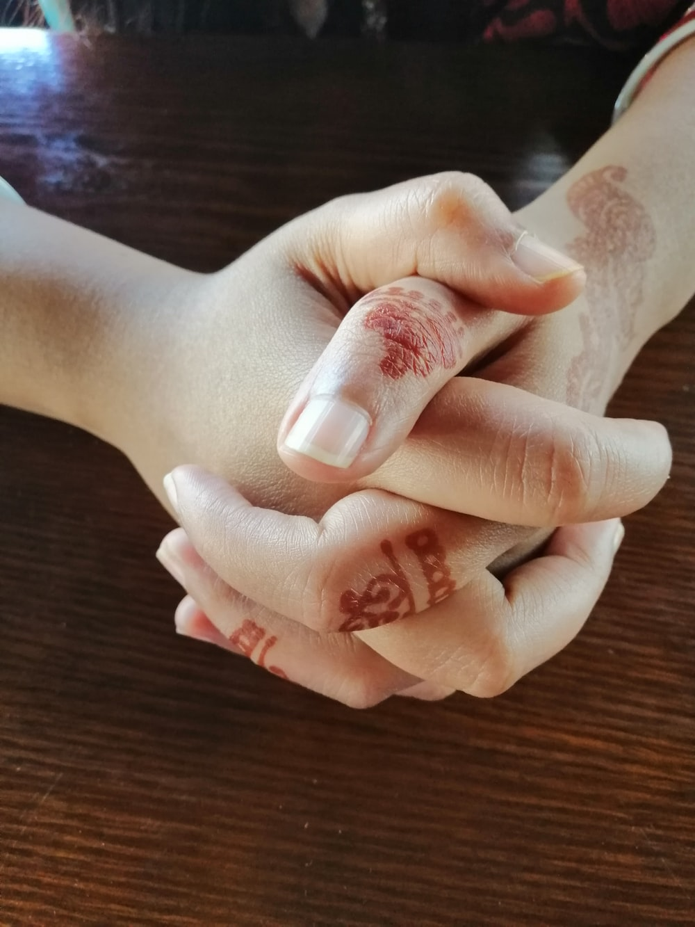 person's hands with red mehndi tattoos