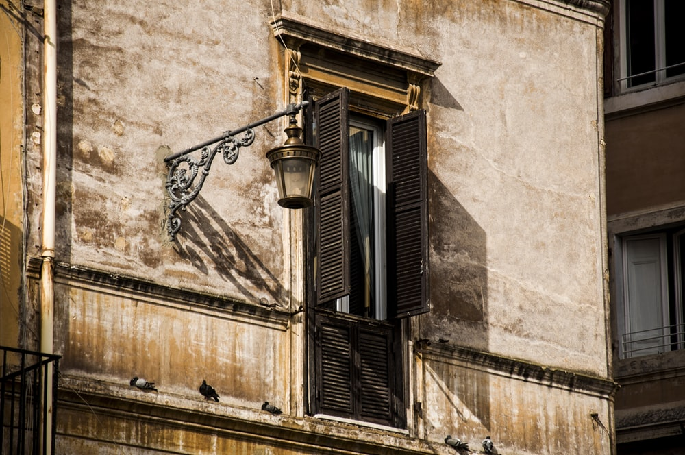 low-angle photo of apartment window with sconce