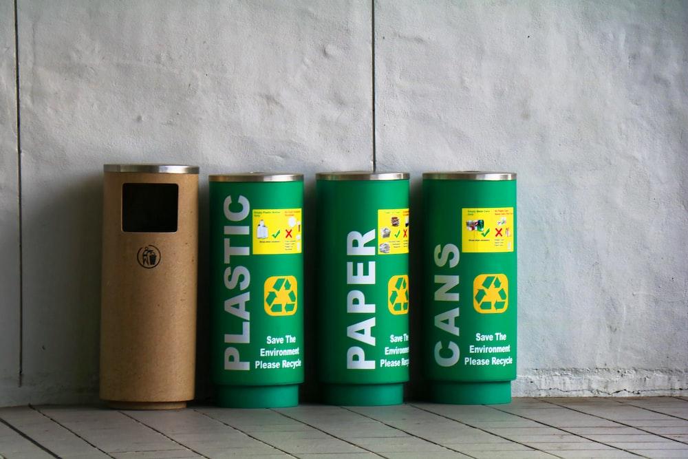 three green and one brown trash bins