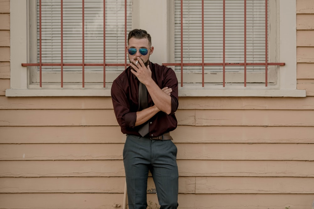 man leaning on wall while smoking