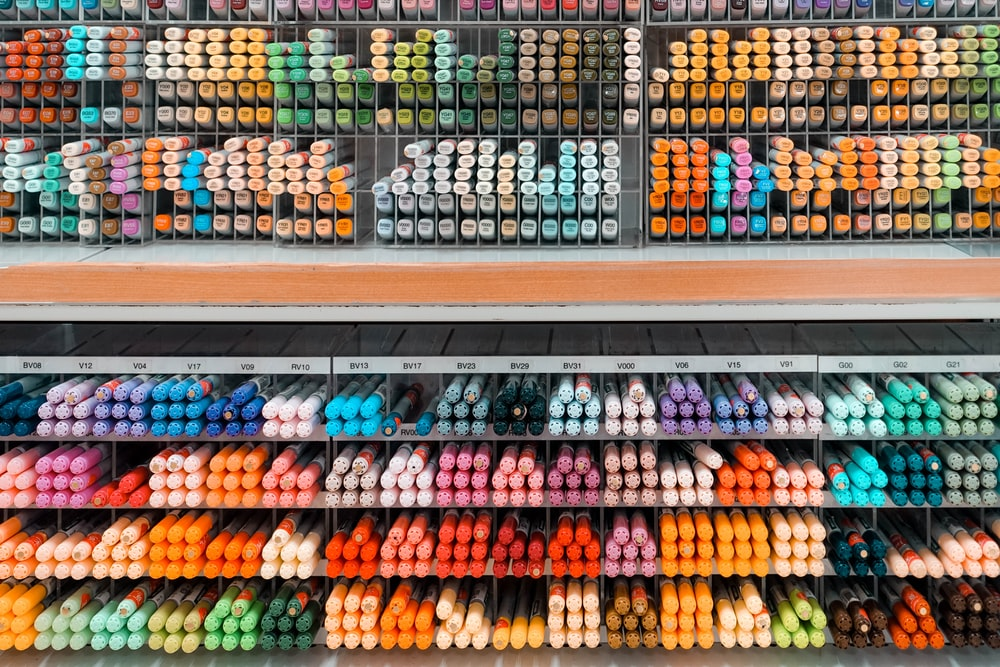 pile of assorted-color pen markers on acrylic rack