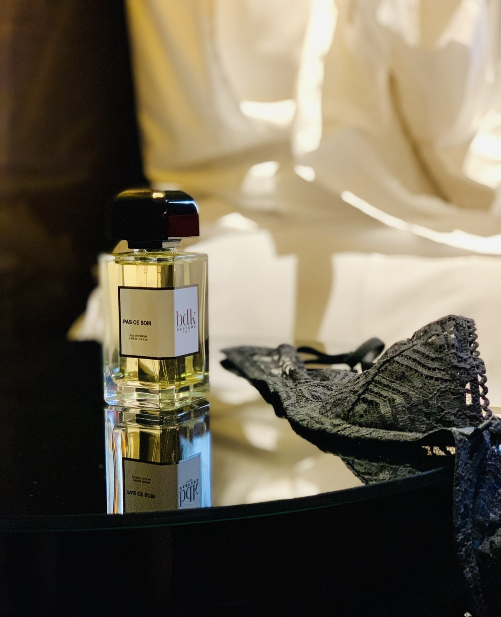 perfume bottle and grey brass on table