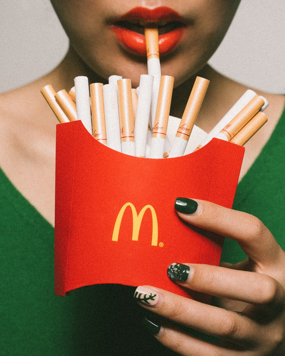 woman holding McDonald's fries pack filled with cigarettes