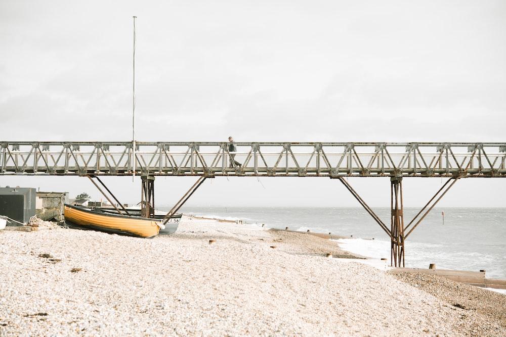 boat on shore under bridge dock
