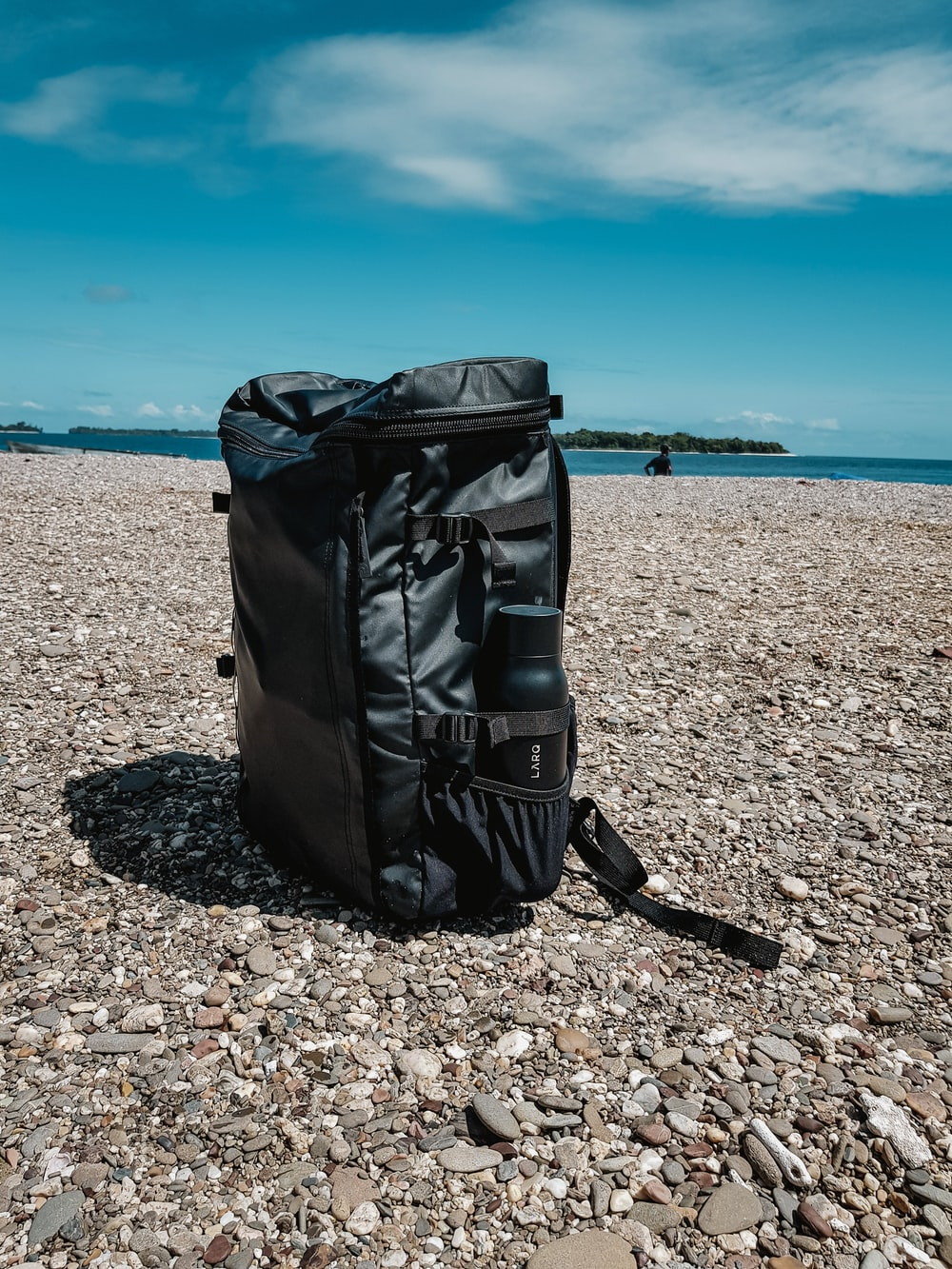 black leather bag on brown rocky beach