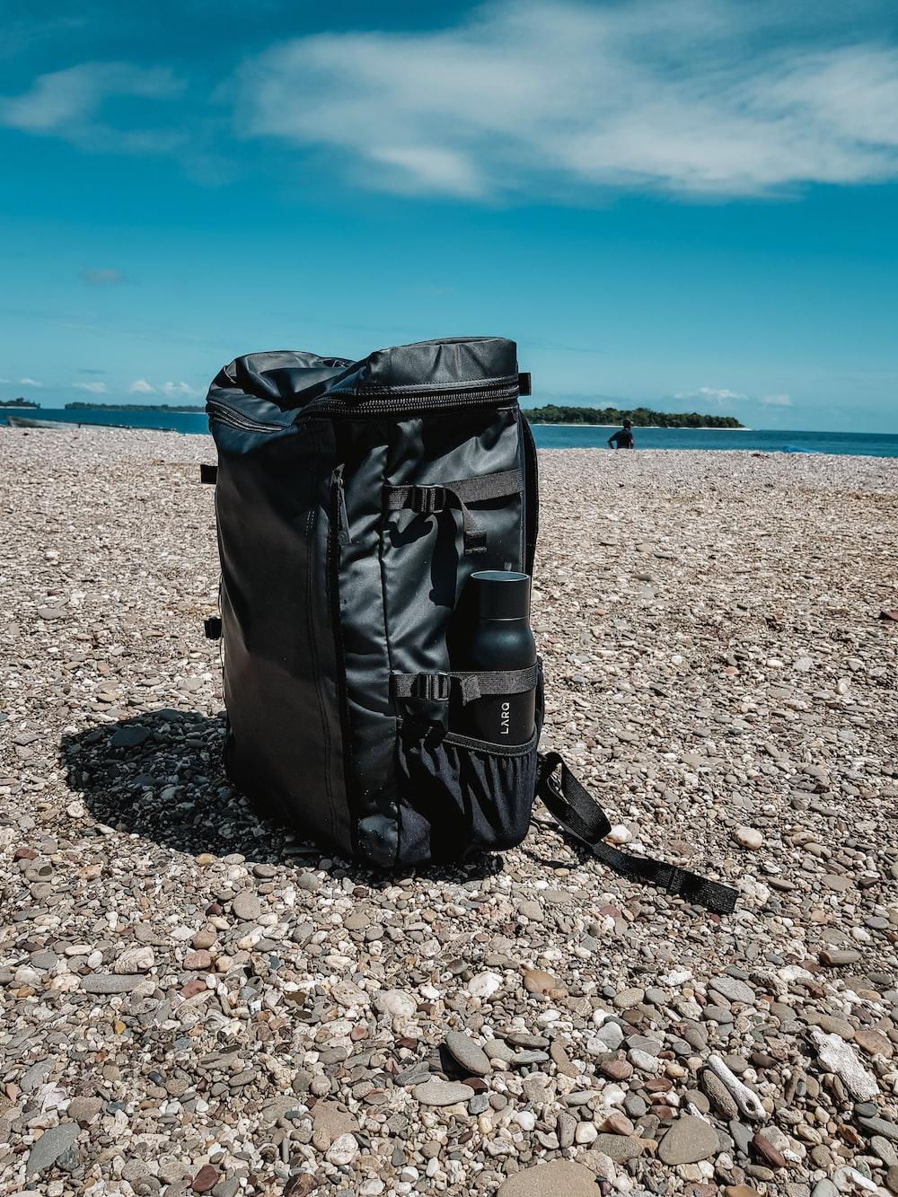 black leather bag on brown rocky beach