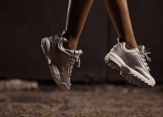 woman jumps using white sneakers