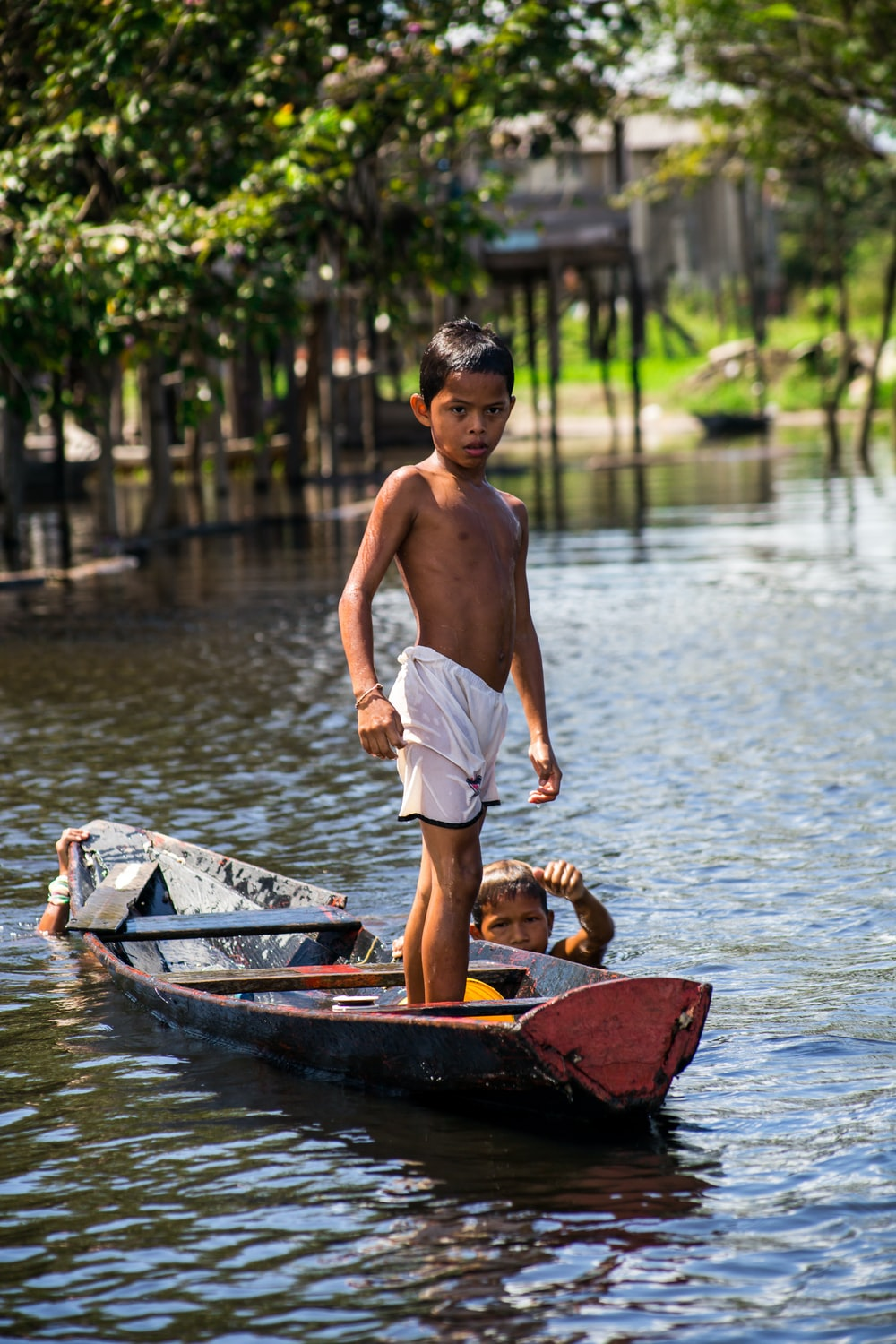 selective focus photography of boy standing on boat