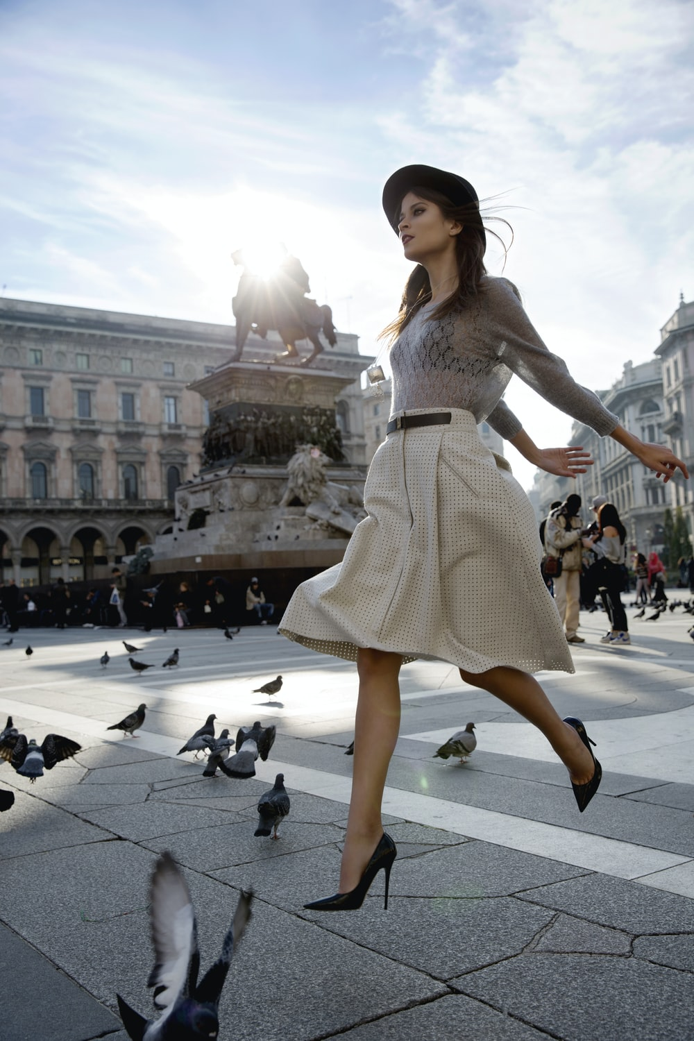 woman crossing the street among pigeons