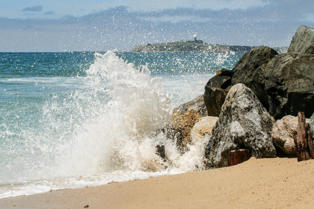 Wave splashing up from a few rocks at a small beach.