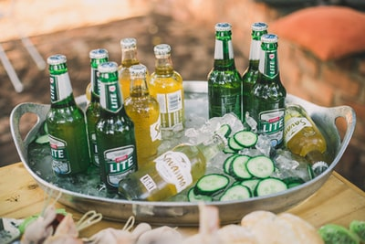 lite beer bottles near sliced zucchini in gray stainless steel bucket cider zoom background