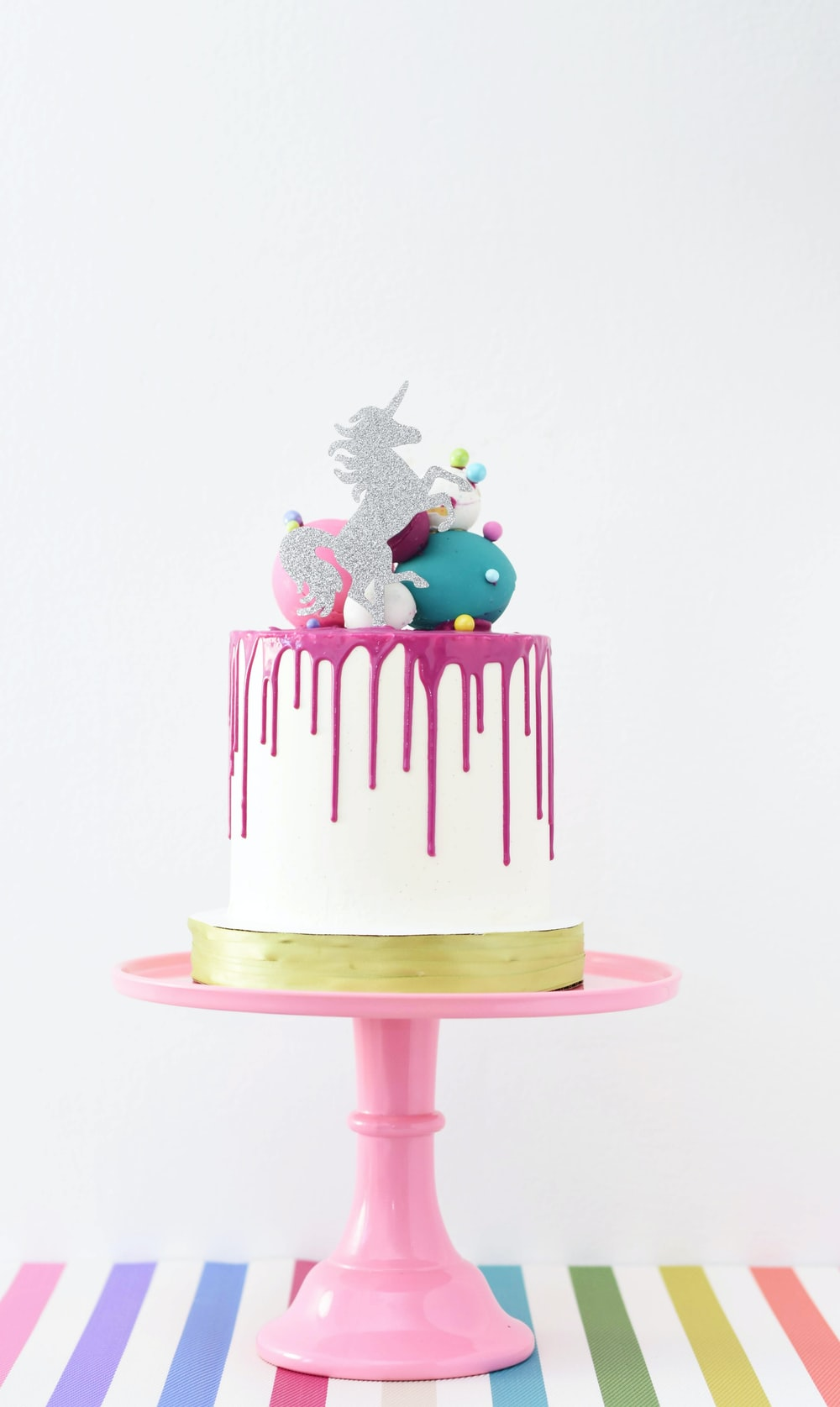 white and pink unicorn cake on a pink stand
