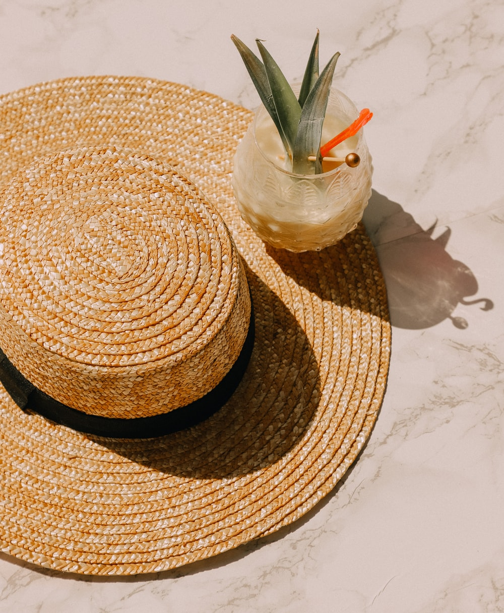 pineapple glass drink on brown sunhat
