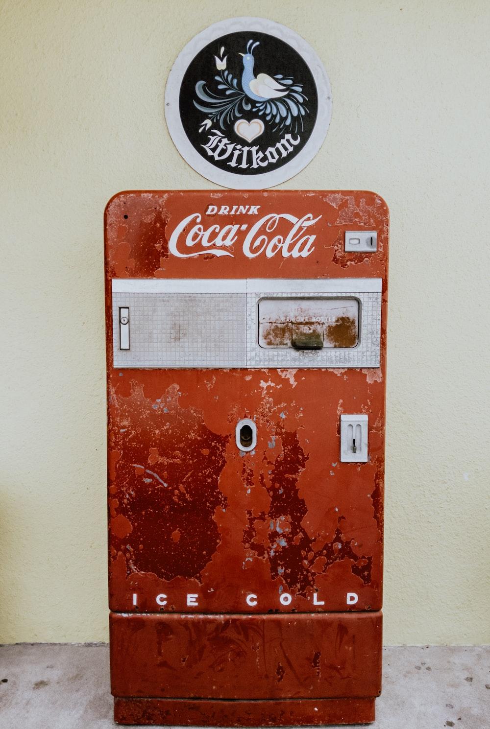 Coca-Cola refrigerator beside wall