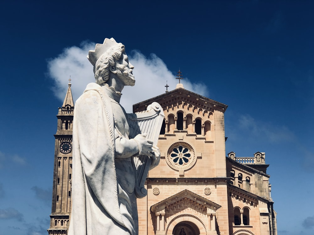 man with harp statue in front of the church building
