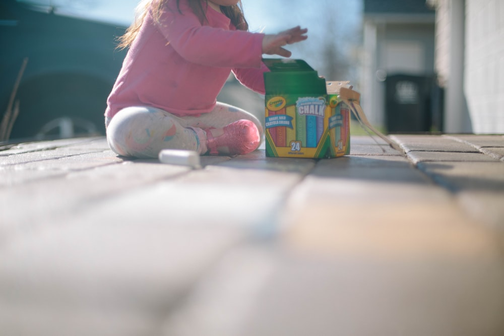 girl sitting beside box of chalk