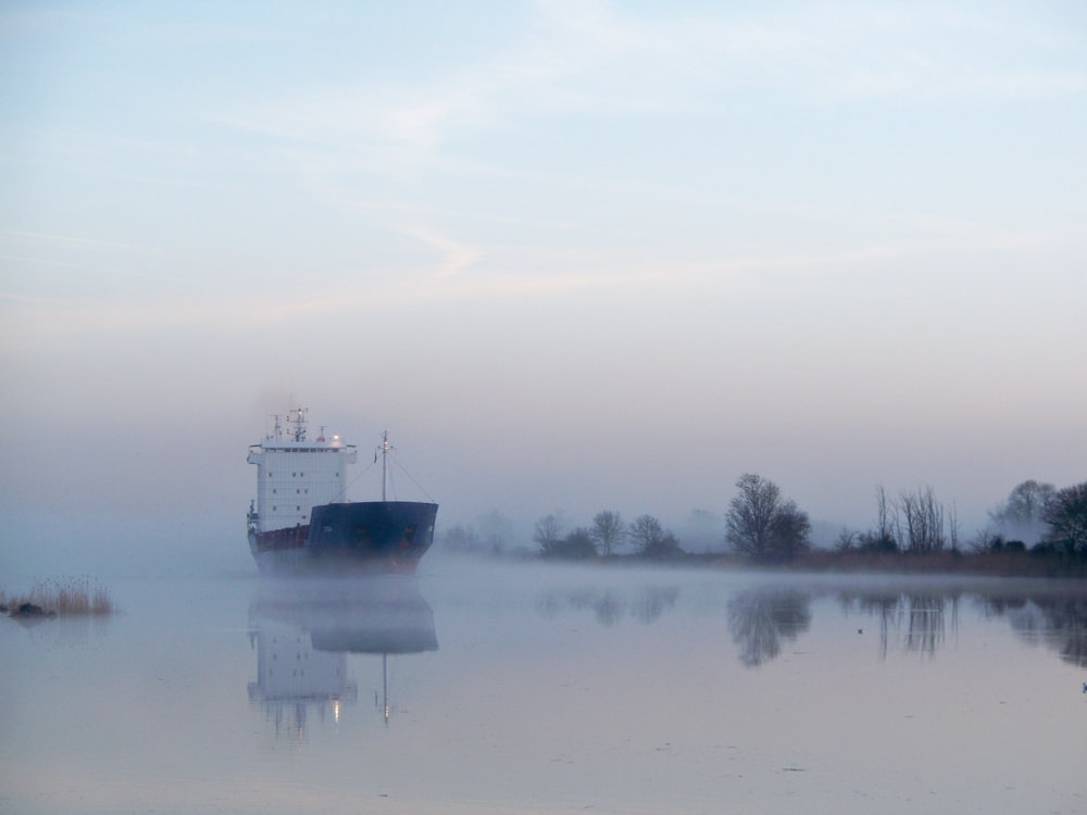 blue and white cargo ship sailing on calm glassy canal with fogs