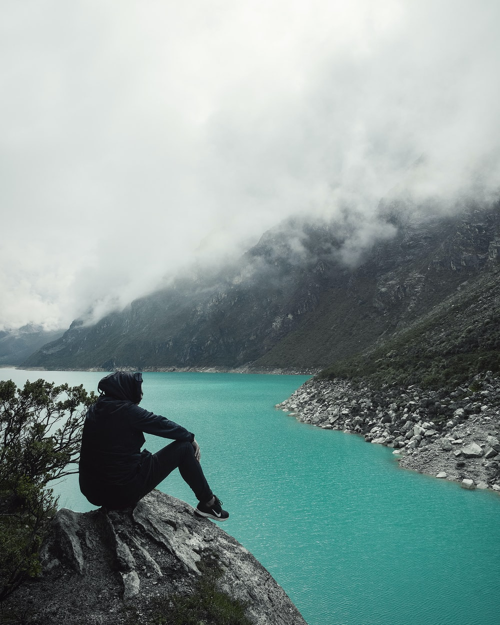 person sitting on cliff with overlooking lake