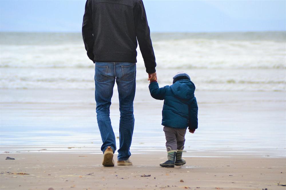 man and boy walking on seashore under blue sky