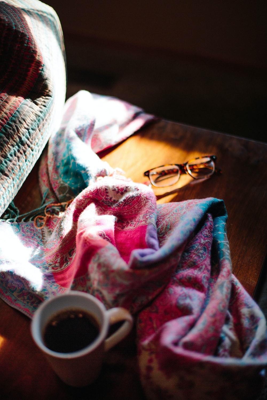 eyeglasses beside blanket and beverage filled mug