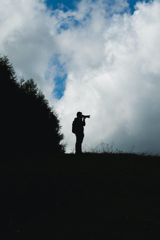 silhouette of man taking photo beside tree