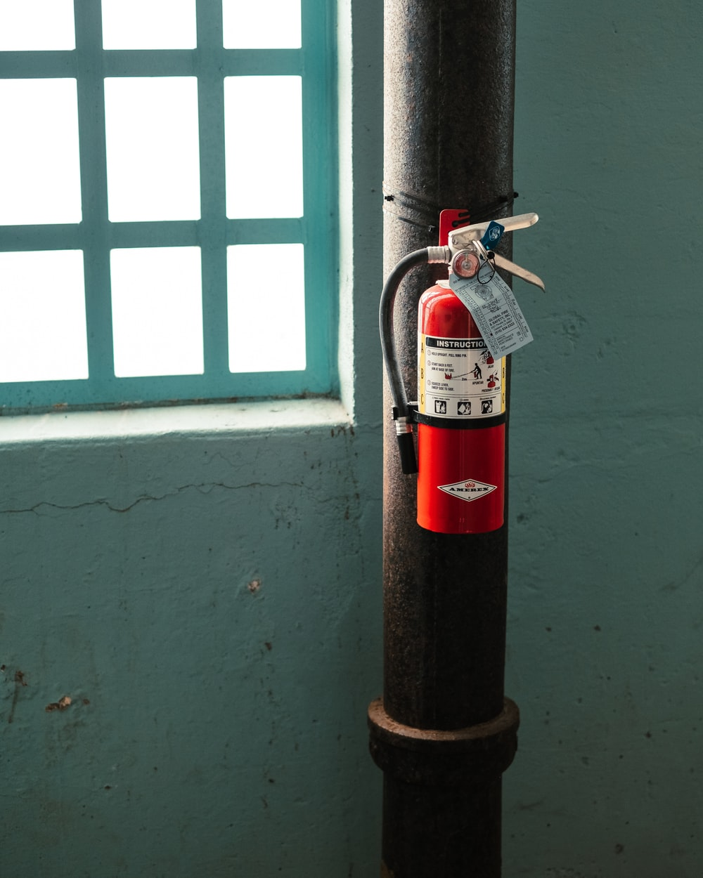 red fire extinguisher on brown metal pipe near window