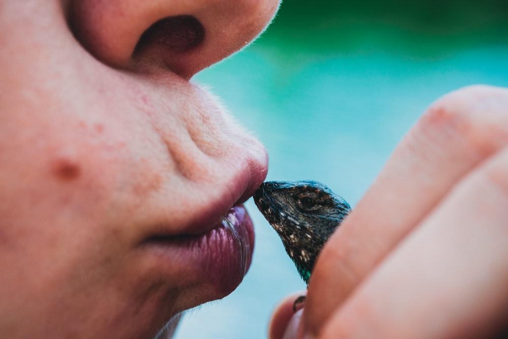 person kissing black lizard