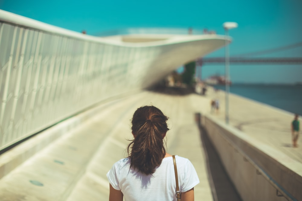 woman wearing white top walking under blue sky during daytime