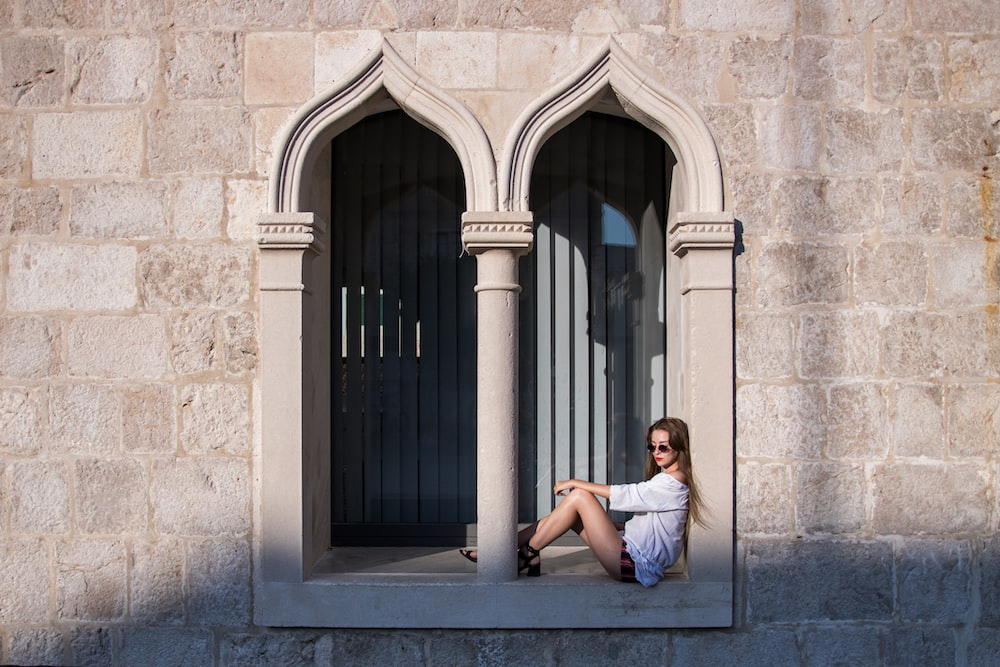 woman sitting on concrete window during daytime