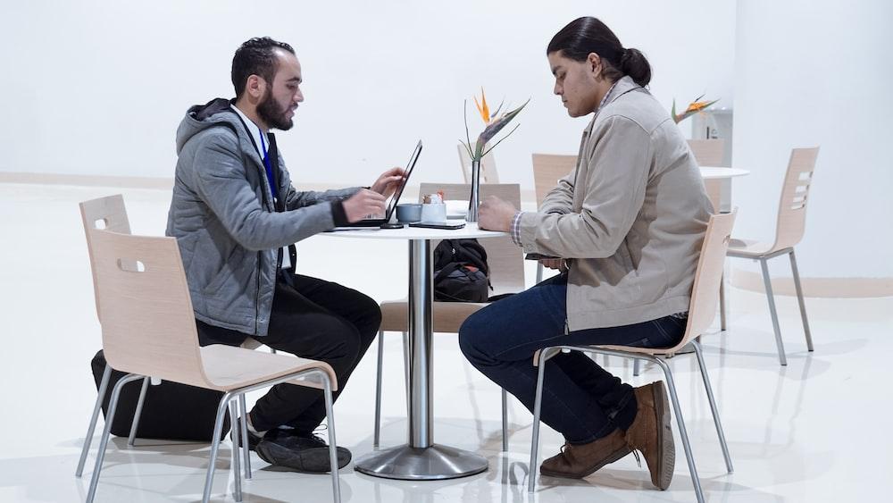 sitting man using laptop near woman sitting beside table