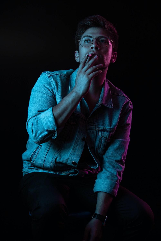 man wearing blue denim button-up jacket smoking cigarette
