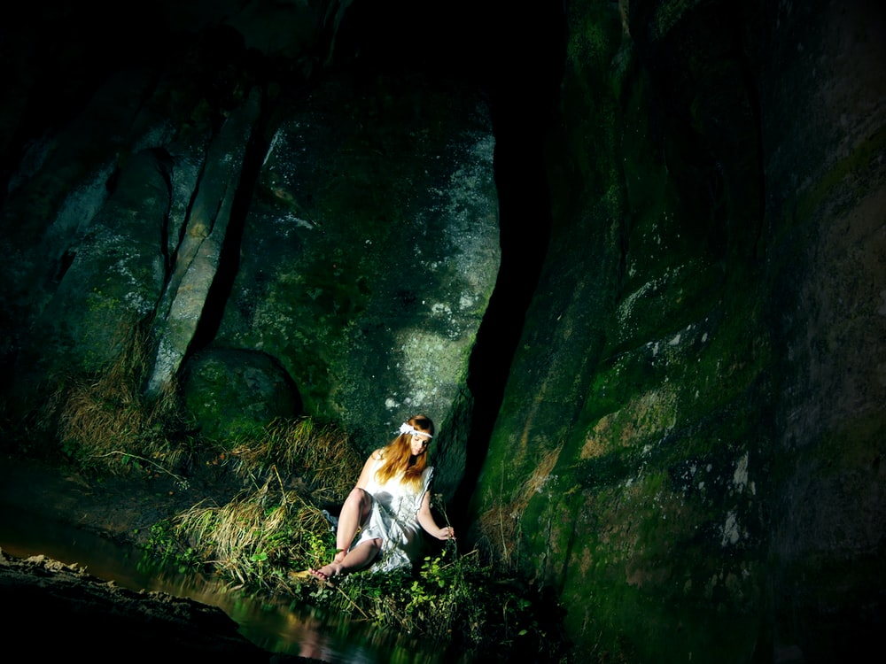woman wearing gray dress sitting beside body of water inside cave